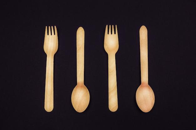Forchette e cucchiai di posate in legno ecologico su sfondo nero