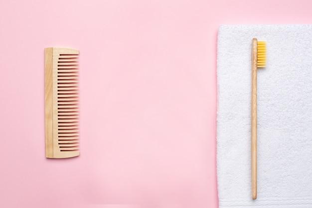 Spazzolino da denti di legno di eco, pettine e asciugamano di bagno bianco sul rosa
