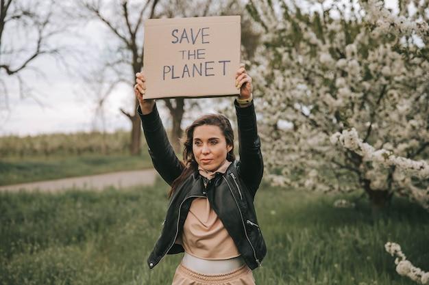 Ecoattivista femminile che tiene il cartello con il riciclo salva il pianeta