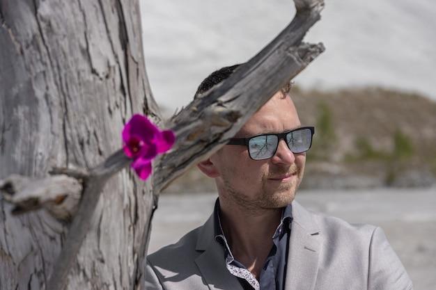 Concetto ecologico. uomo d'affari sta accanto a un albero secco su cui un fiore vivo cresce sullo sfondo di rifiuti chimici da un impianto chimico.