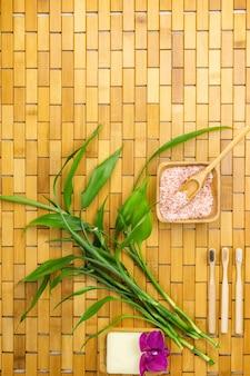 Concetto di prodotti ecologici con sale da bagno, foglie di bambù e spazzolino da denti sul tappetino in legno
