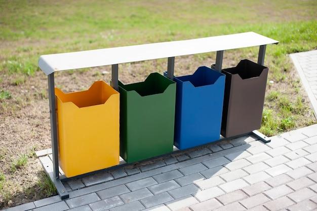 Bidoni della spazzatura ecologici in diversi colori nel parco all'aperto