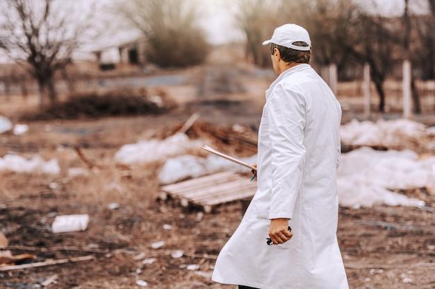 Ecologo in uniforme bianca e cappuccio sulla lavagna per appunti della tenuta della testa mentre camminando sulla discarica.