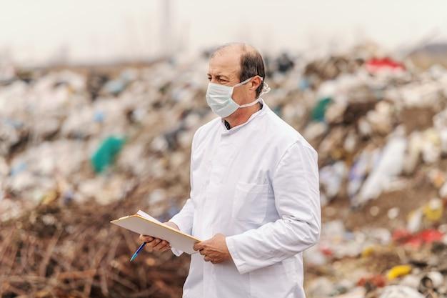 Ecologo in uniforme bianca e maschera sul viso con appunti e valutazione del danno.