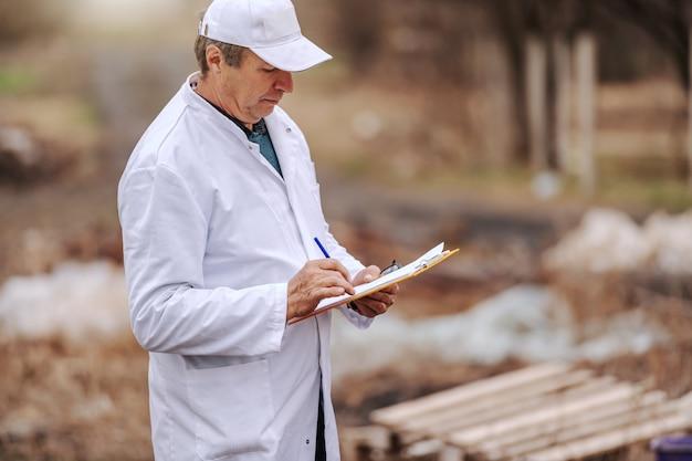 Ecologo in uniforme bianca scrivendo negli appunti i risultati dell'inquinamento del suolo stando in piedi sulla discarica.