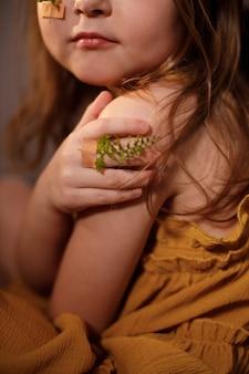 Ecologia e concetto contro la vaccinazione, primo piano di una bambina con rametti di felce incollati con cerotti sulle dita e che copre l'avambraccio con la mano.