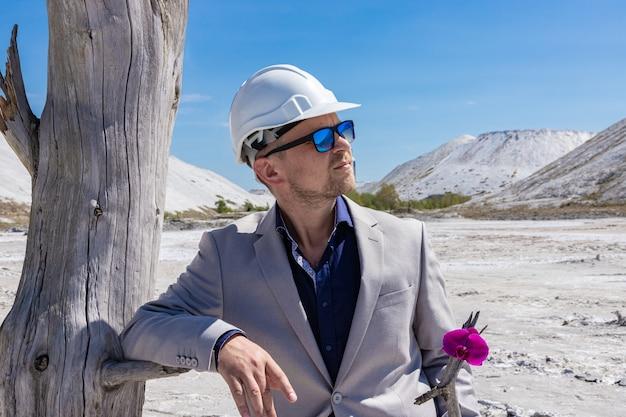 Concetto di ecologia, uomo d'affari conserva fiori di orchidea su uno sfondo di disastro ambientale.