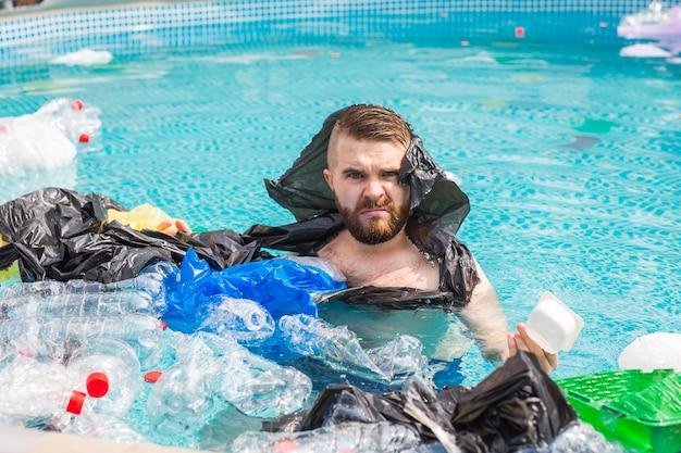 Ecologia, rifiuti di plastica, emergenza ambientale e inquinamento delle acque: un uomo scioccato nuota in una piscina sporca.