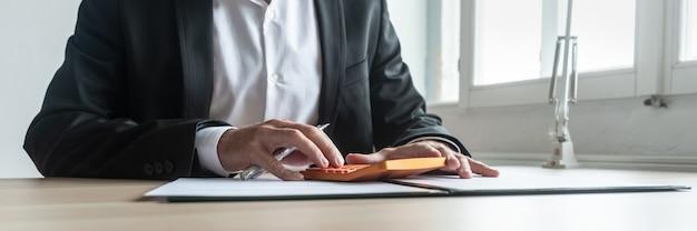 Concetto di economia e finanza - consulente finanziario seduto alla sua scrivania che fa calcoli sulla calcolatrice arancione.