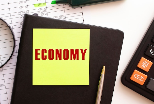 Testo economy su un adesivo sul desktop calcolatrice diario e penna