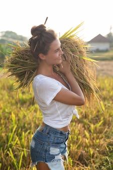 Ecoturismo o lavoro quotidiano. coltivatore di donna felice durante la raccolta sul campo di riso
