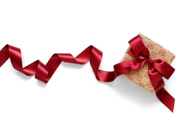 Confezione regalo ecru con nastro di raso rosso scuro isolato su bianco