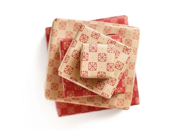 Contenitori di regalo modellati ecru e rossi isolati sulla vista superiore bianca