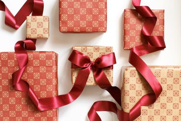 Scatole regalo ecrù e rosse con vista dall'alto del nastro rosso
