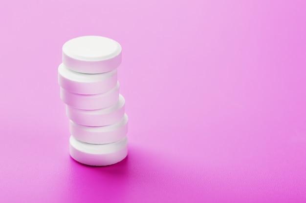 Pillole di ecstasy in fila su una superficie rosa isolare