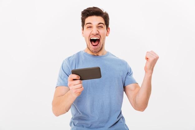 Uomo estatico in maglietta casuale che si rallegra della sua vittoria mentre giocando ai giochi online sul telefono cellulare, isolato sopra la parete bianca
