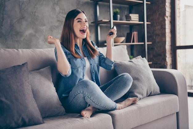 Una studentessa estatica positiva si siede sul divano a piedi nudi e tiene il telecomando