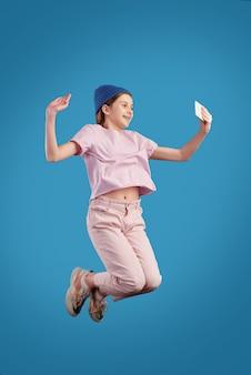 Estatica ragazza adolescente in abbigliamento casual tenendo lo smartphone davanti a se stessa mentre fa selfie nel salto su sfondo blu