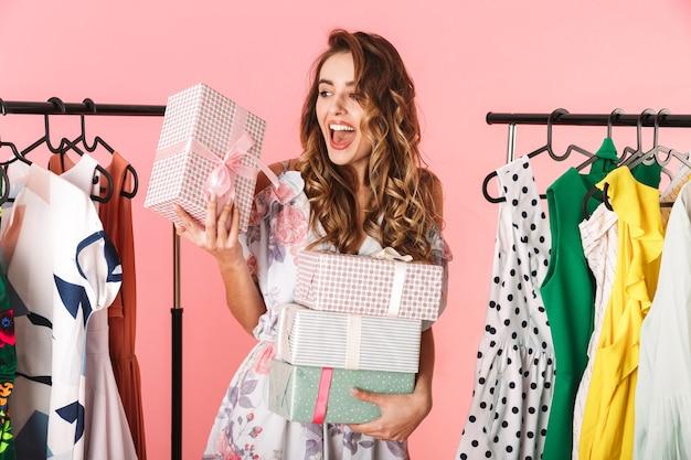 Estatica donna che indossa un abito in piedi in negozio vicino appendiabiti con scatole presenti isolato sul rosa