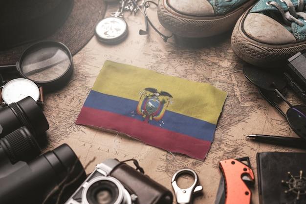 Bandiera dell'ecuador tra gli accessori del viaggiatore sulla vecchia mappa d'annata. concetto di destinazione turistica.