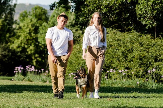 Uomo ecuadoriano e donna caucasica che portano a spasso il loro cane nel parco. giovani coppie moderne