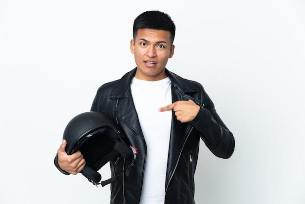 Uomo ecudorian con un casco da motociclista isolato su priorità bassa bianca con l'espressione facciale di sorpresa