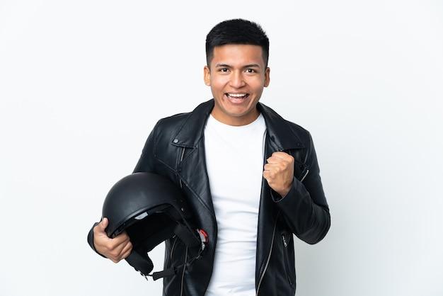 Uomo ecudoriano con un casco da motociclista isolato sul muro bianco che celebra una vittoria nella posizione del vincitore