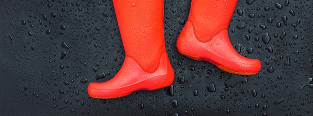 I bordi degli stivali da pioggia arancioni sono su una superficie bagnata bagnata coperta di gocce di pioggia.