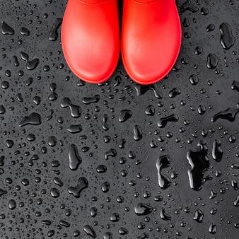 I bordi degli stivali di gomma rossi si trovano su una superficie bagnata bagnata coperta di gocce di pioggia. vista dall'alto.