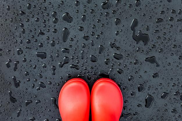 I bordi degli stivali di gomma rossi si trovano su una superficie bagnata bagnata coperta di gocce di pioggia