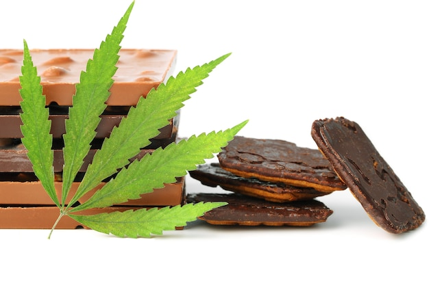 Barrette di cioccolato alimentare di marijuana medica commestibile e biscotti al cioccolato con foglia di canapa verde isolato