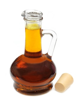 Olio di senape commestibile in una bottiglia trasparente su sfondo bianco