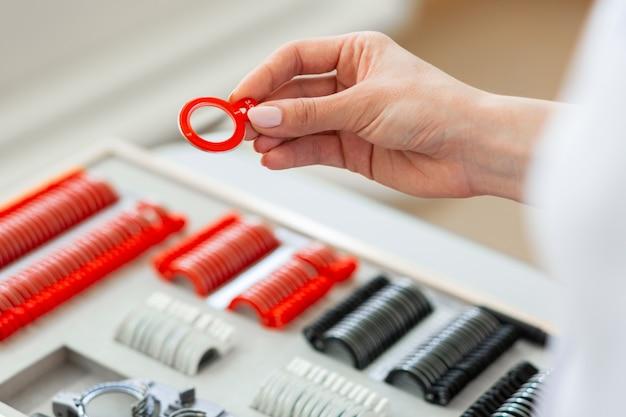 Oculista professionista istruito che porta lenti in speciale copertura rossa
