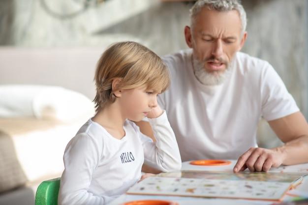 Formazione scolastica. un ragazzo che legge un libro insieme a suo nonno