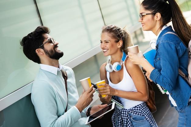 Istruzione, campus, amicizia e concetto di persone. gruppo di studenti felici con cartelle scolastiche all'aperto