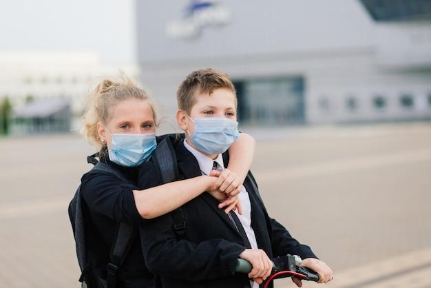 Concetto di educazione, infanzia e persone. bambini in età scolare felici con zaini e scooter all'aperto in maschera protettiva