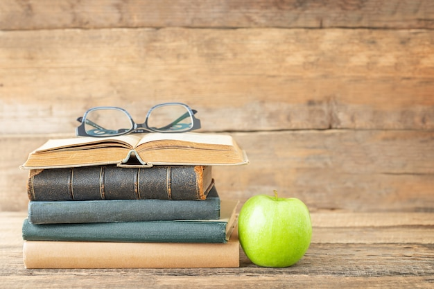 Il concetto di educazione libri mela verde e bicchieri sul libro aperto su uno sfondo di legno