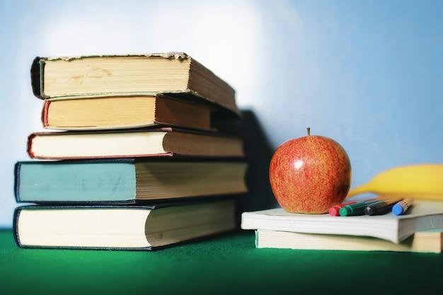 Pila di libri di concetto di istruzione, mela e penna