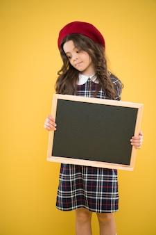 Concetto di educazione. ragazza felice in berretto francese. cartellone pubblicitario per la promozione. vendite della spesa scolastica. bambino su sfondo giallo. di nuovo a scuola. piccola ragazza con tabellone scolastico, copia spazio.