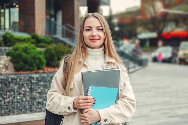 Concetto di educazione. la ragazza felice dello studente tiene i libri dei quaderni delle cartelle nei sorrisi delle mani contro un edificio universitario moderno
