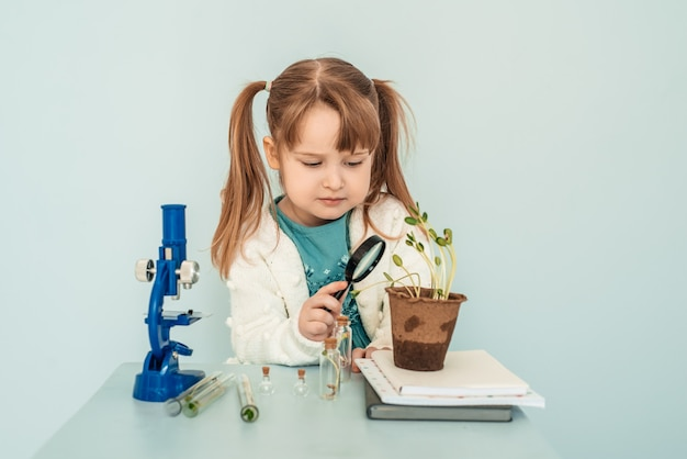Concetto di educazione. la piccola neonata guarda i microscopi in laboratorio.
