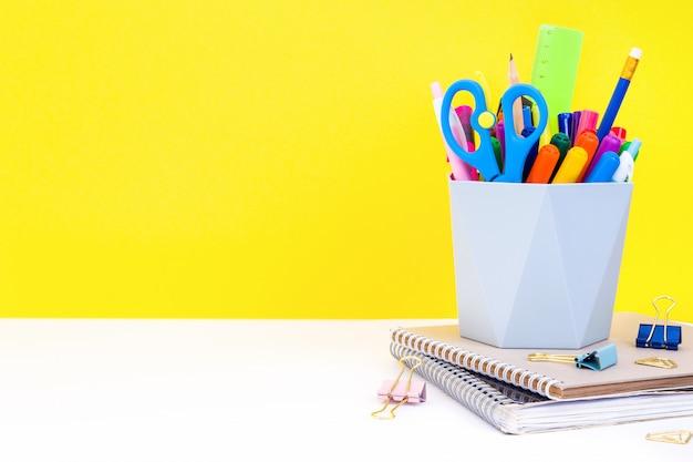 Concetto di educazione: quaderni, cancelleria e organizer grigio con penne multicolori, pennarelli, matite e forbici su un tavolo bianco in classe su giallo