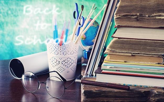 Concetto di educazione. una pila di libri di testo e un libro sulla scrivania con gli occhiali e un computer. mela e compiti della colazione della scuola