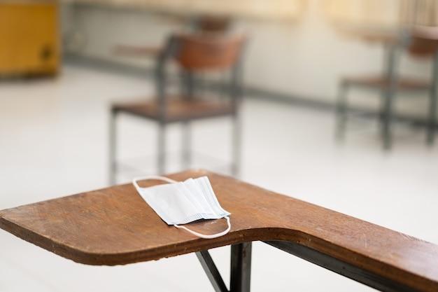 Educazione durante covid-19: una maschera facciale medica usata è appesa a una sedia da conferenza in legno in un'aula vuota durante la pandemia di covid-19