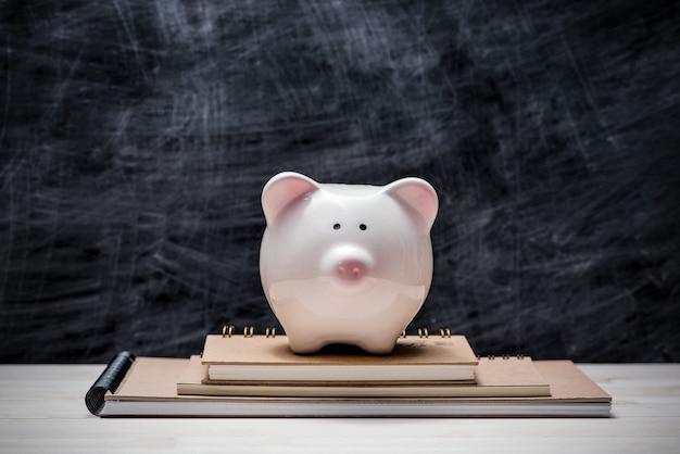 Risparmio finanziario per l'istruzione. salvadanaio rosa sopra i libri con la lavagna.