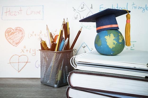 Concetto di studio laureato in formazione cappello di laurea sulle matite con grafico di equazione aritmetica formula