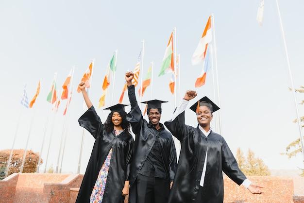 Concetto di educazione, laurea e persone - gruppo di studenti internazionali felici in tavole di mortaio e abiti da scapolo con diplomi