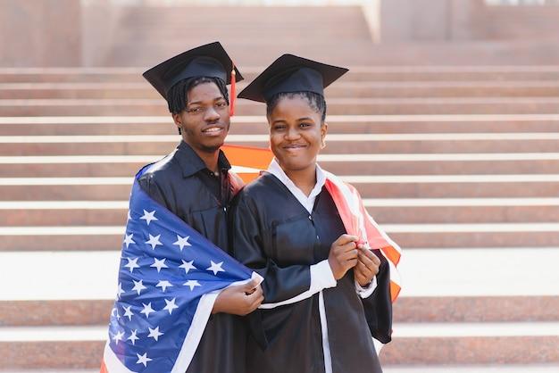 Concetto di educazione, laurea e persone - studenti internazionali felici in tavole di mortaio e abiti da scapolo con bandiera americana