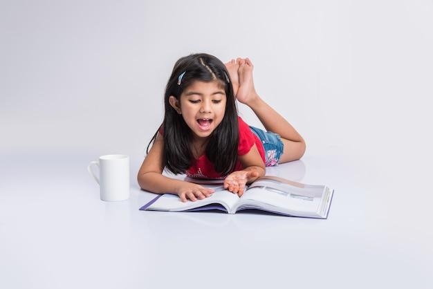 Concetto di educazione a casa - piccola ragazza indiana o asiatica carina che studia con una pila di libri e una tazza da caffè mentre è seduta sul pavimento a casa. isolato su sfondo bianco