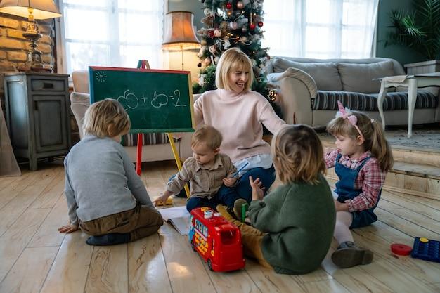 Istruzione, concetto di persone di scuola materna. insegnante di giovane donna con bambini che giocano insieme